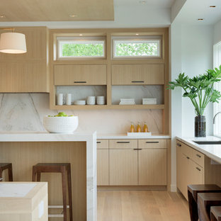 Large modern u-shaped open plan kitchen in Minneapolis with an undermount sink, flat-panel cabinets, light wood cabinets, marble benchtops, white splashback, stone slab splashback, panelled appliances, light hardwood floors and multiple islands.