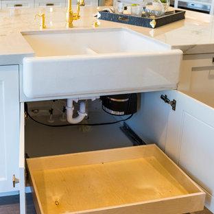 ソルトレイクシティの巨大なトランジショナルスタイルのおしゃれなキッチン (エプロンフロントシンク、シェーカースタイル扉のキャビネット、白いキャビネット、珪岩カウンター、白いキッチンパネル、石スラブのキッチンパネル、パネルと同色の調理設備、無垢フローリング、茶色い床) の写真