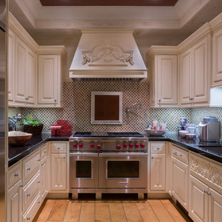 Small mediterranean enclosed kitchen inspiration - Inspiration for a small mediterranean u-shaped light wood floor enclosed kitchen remodel in Orange County with a single-bowl sink, raised-panel cabinets, beige cabinets, granite countertops, multicolored backsplash, mosaic tile backsplash, stainless steel appliances and no island
