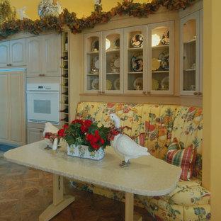 Geschlossene, Große Eklektische Küche in U-Form mit profilierten Schrankfronten, Schränken im Used-Look, Granit-Arbeitsplatte, Elektrogeräten mit Frontblende, braunem Holzboden und Kücheninsel in San Luis Obispo
