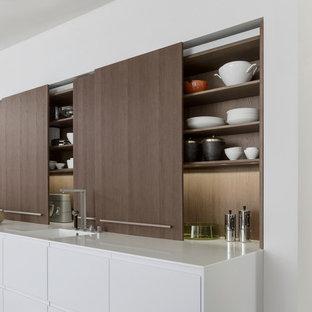 На фото: кухня-гостиная среднего размера в стиле модернизм с плоскими фасадами, темными деревянными фасадами, столешницей из кварцита, техникой из нержавеющей стали, островом, монолитной раковиной и бетонным полом