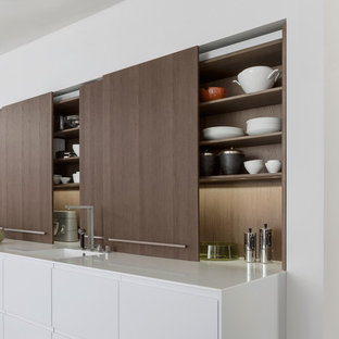 Ejemplo de cocina en U, moderna, de tamaño medio, abierta, con armarios con paneles lisos, puertas de armario de madera en tonos medios, encimera de cuarcita, electrodomésticos de acero inoxidable, una isla, fregadero integrado y suelo de cemento