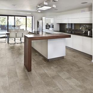 ボイシの広いコンテンポラリースタイルのおしゃれなキッチン (アンダーカウンターシンク、フラットパネル扉のキャビネット、白いキャビネット、人工大理石カウンター、黒いキッチンパネル、ガラス板のキッチンパネル、シルバーの調理設備、セラミックタイルの床) の写真