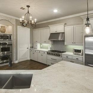 Foto på ett mellanstort vintage kök, med en undermonterad diskho, luckor med upphöjd panel, vita skåp, grått stänkskydd, rostfria vitvaror, mörkt trägolv och en halv köksö