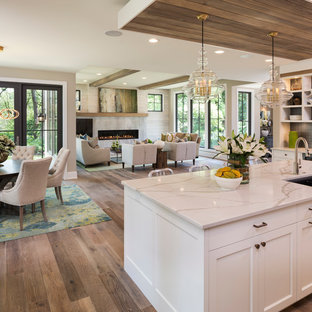 Large transitional eat-in kitchen pictures - Example of a large transitional single-wall dark wood floor and brown floor eat-in kitchen design in Minneapolis with an undermount sink, shaker cabinets, white cabinets, marble countertops, white backsplash, stone slab backsplash, stainless steel appliances and an island