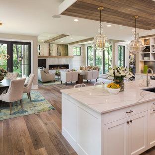 Idée de décoration pour une cuisine ouverte tradition avec un évier encastré, un placard à porte shaker, des portes de placard blanches, une crédence noire, un sol en bois clair et un îlot central.