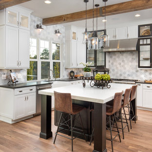 Farmhouse kitchen ideas - Country u-shaped medium tone wood floor and brown floor kitchen photo in Columbus with a farmhouse sink, shaker cabinets, white cabinets, gray backsplash, stainless steel appliances, an island and black countertops