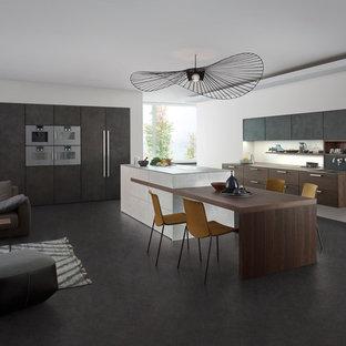 Esempio di una cucina moderna di medie dimensioni con lavello da incasso, ante lisce, ante grigie, top in superficie solida, paraspruzzi bianco, elettrodomestici in acciaio inossidabile, pavimento in cemento e isola