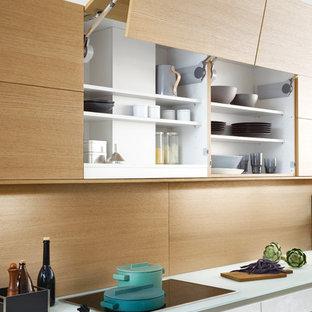 На фото: параллельная кухня-гостиная среднего размера в стиле модернизм с врезной раковиной, плоскими фасадами, белыми фасадами, стеклянной столешницей, техникой из нержавеющей стали, бетонным полом и островом с