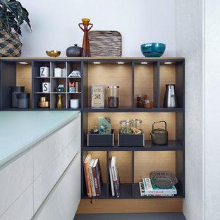 Immagine di una cucina moderna di medie dimensioni con ante lisce, ante bianche, top in vetro, pavimento in cemento, isola, lavello sottopiano e elettrodomestici in acciaio inossidabile