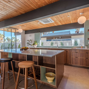 This is an example of a mid-sized midcentury l-shaped eat-in kitchen in Los Angeles with an undermount sink, flat-panel cabinets, dark wood cabinets, quartzite benchtops, green splashback, ceramic splashback, stainless steel appliances, concrete floors and with island.