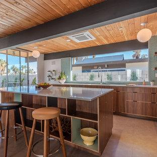 ロサンゼルスの中くらいのミッドセンチュリースタイルのおしゃれなキッチン (アンダーカウンターシンク、フラットパネル扉のキャビネット、濃色木目調キャビネット、珪岩カウンター、緑のキッチンパネル、セラミックタイルのキッチンパネル、シルバーの調理設備、コンクリートの床) の写真