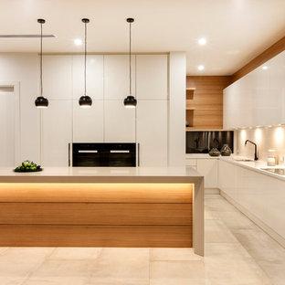 アデレードの広いコンテンポラリースタイルのおしゃれなキッチン (フラットパネル扉のキャビネット、白いキャビネット、白いキッチンパネル、ガラス板のキッチンパネル、黒い調理設備、ベージュの床) の写真