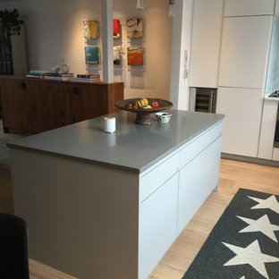 Inspiration for a medium sized contemporary l-shaped kitchen/diner in London with a built-in sink, flat-panel cabinets, white cabinets, granite worktops, white splashback, stone slab splashback, integrated appliances, light hardwood flooring and an island.