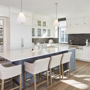 Modelo de cocina en L, marinera, grande, abierta, con electrodomésticos de acero inoxidable, armarios estilo shaker, puertas de armario blancas, salpicadero marrón, salpicadero de azulejos tipo metro, suelo de madera en tonos medios y una isla