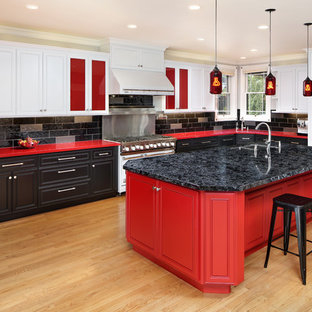 Transitional u-shaped kitchen in San Francisco with a double-bowl sink, beaded inset cabinets, red cabinets, black splashback, panelled appliances, light hardwood floors, with island, beige floor and red benchtop.