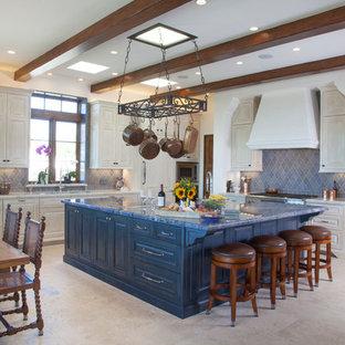 サンディエゴの広い地中海スタイルのおしゃれなキッチン (レイズドパネル扉のキャビネット、ベージュのキャビネット、青いキッチンパネル、ドロップインシンク、クオーツストーンカウンター、セラミックタイルのキッチンパネル、シルバーの調理設備、トラバーチンの床) の写真