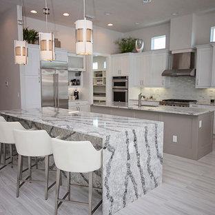 Esempio di una grande cucina minimalista con lavello sottopiano, ante con riquadro incassato, ante grigie, top in marmo, paraspruzzi grigio, paraspruzzi in lastra di pietra, elettrodomestici in acciaio inossidabile, pavimento in marmo e 2 o più isole