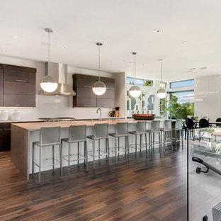 Immagine di una grande cucina abitabile design con lavello sottopiano, ante lisce, ante in legno bruno, top in cemento, paraspruzzi bianco, elettrodomestici in acciaio inossidabile, parquet scuro, isola, pavimento marrone e paraspruzzi con lastra di vetro