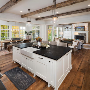 Design ideas for an eclectic galley open plan kitchen with a drop-in sink, white cabinets, granite benchtops, medium hardwood floors, with island and brown floor.