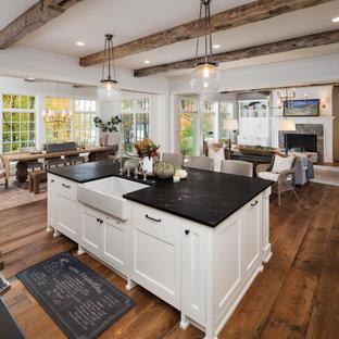 エクレクティックスタイルのおしゃれなキッチン (ドロップインシンク、白いキャビネット、御影石カウンター、無垢フローリング、茶色い床) の写真