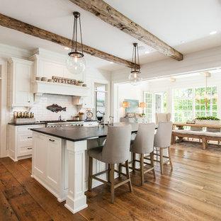 カントリー風おしゃれなキッチン (白いキャビネット、御影石カウンター、白いキッチンパネル、シルバーの調理設備の、無垢フローリング、茶色い床、シェーカースタイル扉のキャビネット、サブウェイタイルのキッチンパネル、黒いキッチンカウンター) の写真