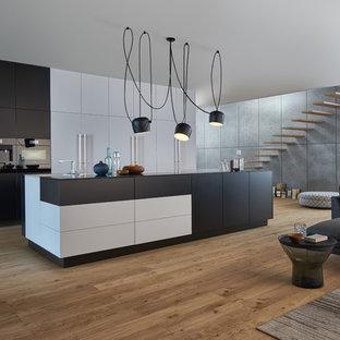 Einzeilige, Geräumige Moderne Wohnküche mit flächenbündigen Schrankfronten, schwarzen Schränken, Kücheninsel, Unterbauwaschbecken, Mineralwerkstoff-Arbeitsplatte, schwarzen Elektrogeräten und hellem Holzboden in New York
