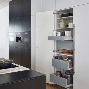 Idéer för att renovera ett mycket stort funkis linjärt kök och matrum, med en undermonterad diskho, släta luckor, svarta skåp, bänkskiva i koppar, svarta vitvaror, ljust trägolv och en köksö