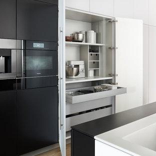 Источник вдохновения для домашнего уюта: огромная прямая кухня в стиле модернизм с врезной раковиной, плоскими фасадами, черными фасадами, столешницей из акрилового камня, черной техникой, светлым паркетным полом и островом