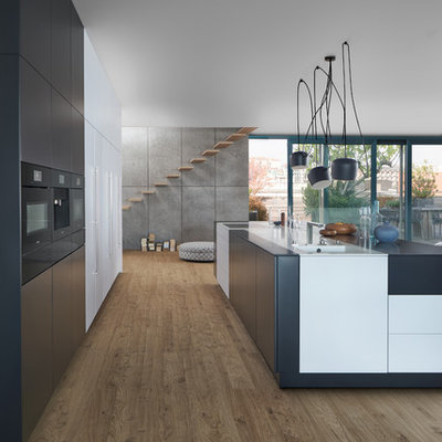 Example of a huge minimalist galley light wood floor eat-in kitchen design in New York with an undermount sink, flat-panel cabinets, black cabinets, solid surface countertops, black appliances and an island
