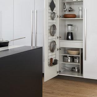 Idee per un'ampia cucina moderna con lavello sottopiano, ante lisce, ante nere, top in superficie solida, elettrodomestici neri, parquet chiaro e isola