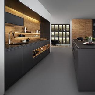 Einzeilige, Große Moderne Wohnküche mit Doppelwaschbecken, flächenbündigen Schrankfronten, grauen Schränken, Mineralwerkstoff-Arbeitsplatte, Küchenrückwand in Braun, Küchengeräten aus Edelstahl, Betonboden und Kücheninsel in New York