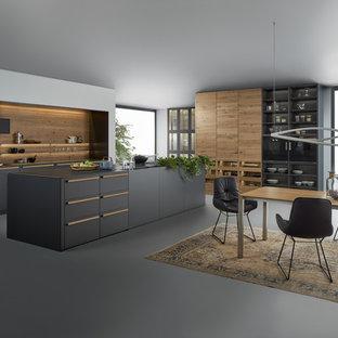 Cette image montre une grande cuisine américaine linéaire minimaliste avec un placard à porte plane, des portes de placard grises, un plan de travail en surface solide, une crédence marron, un électroménager en acier inoxydable, béton au sol, un îlot central et un évier 2 bacs.