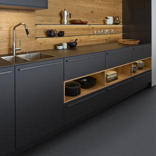 Идея дизайна: большая прямая кухня-гостиная в стиле модернизм с двойной раковиной, плоскими фасадами, серыми фасадами, столешницей из акрилового камня, коричневым фартуком, техникой из нержавеющей стали, бетонным полом и островом