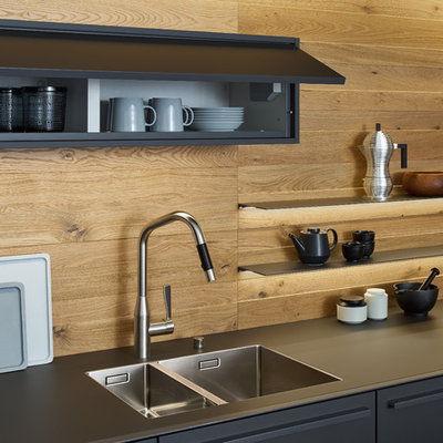 Eat-in kitchen - large modern single-wall concrete floor eat-in kitchen idea in New York with a double-bowl sink, flat-panel cabinets, gray cabinets, solid surface countertops, brown backsplash, stainless steel appliances and an island