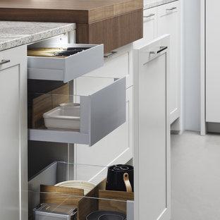ニューヨークの広いモダンスタイルのおしゃれなキッチン (エプロンフロントシンク、シェーカースタイル扉のキャビネット、白いキャビネット、ラミネートカウンター、茶色いキッチンパネル、シルバーの調理設備、コンクリートの床) の写真