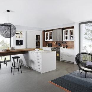 Foto di una grande cucina moderna con lavello stile country, ante in stile shaker, ante bianche, top in laminato, paraspruzzi marrone, elettrodomestici in acciaio inossidabile, pavimento in cemento e penisola