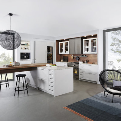 Inspiration for a large modern l-shaped concrete floor eat-in kitchen remodel in New York with a farmhouse sink, shaker cabinets, white cabinets, laminate countertops, brown backsplash, stainless steel appliances and a peninsula