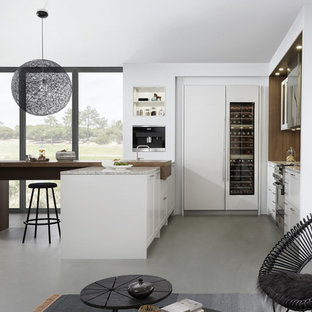 Large modern eat-in kitchen pictures - Inspiration for a large modern l-shaped concrete floor eat-in kitchen remodel in New York with a farmhouse sink, shaker cabinets, white cabinets, laminate countertops, brown backsplash, stainless steel appliances and a peninsula