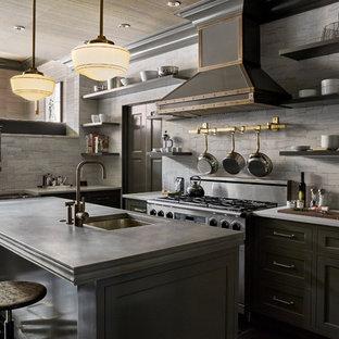 Idée de décoration pour une cuisine victorienne en L avec un évier encastré, un placard à porte shaker, des portes de placard grises, une crédence grise, une crédence en carrelage métro, un électroménager en acier inoxydable, un îlot central et un sol noir.
