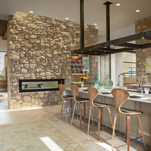 Cette image montre une cuisine sud-ouest américain de taille moyenne avec un électroménager en acier inoxydable, un sol beige, un évier encastré, un placard à porte plane, des portes de placard en bois clair, une crédence grise, une crédence en carrelage de pierre, un sol en travertin, un îlot central et un plan de travail blanc.