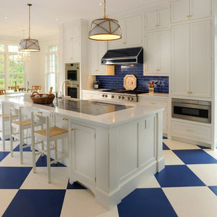 Large traditional eat-in kitchen appliance - Inspiration for a large timeless single-wall porcelain floor and multicolored floor eat-in kitchen remodel in New York with a farmhouse sink, shaker cabinets, white cabinets, blue backsplash, subway tile backsplash, stainless steel appliances, an island and solid surface countertops