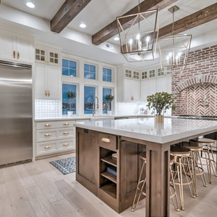 Design ideas for a country l-shaped kitchen in Other with a farmhouse sink, raised-panel cabinets, white cabinets, grey splashback, brick splashback, stainless steel appliances, light hardwood floors, an island, beige floor and white benchtop.