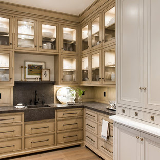 Photo of a traditional l-shaped kitchen pantry in Salt Lake City with an integrated sink, recessed-panel cabinets, distressed cabinets, grey splashback, light hardwood floors and beige floor.