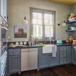 Photo of a small traditional u-shaped kitchen in Houston with a farmhouse sink, shaker cabinets, blue cabinets, window splashback, stainless steel appliances, dark hardwood floors, brown floor and no island.