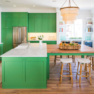 Large beach style u-shaped eat-in kitchen in Minneapolis with a farmhouse sink, shaker cabinets, green cabinets, marble benchtops, white splashback, ceramic splashback, stainless steel appliances, medium hardwood floors, multiple islands, brown floor and white benchtop.