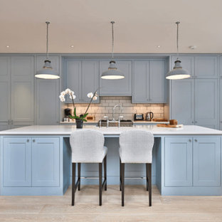 Inspiration for a mid-sized transitional galley open plan kitchen in Other with a double-bowl sink, raised-panel cabinets, blue cabinets, green splashback, ceramic splashback, vinyl floors, with island, quartz benchtops, coloured appliances and beige floor.