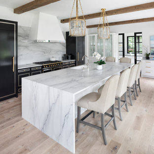 Kitchen - contemporary light wood floor and beige floor kitchen idea in Minneapolis with an undermount sink, black cabinets, marble countertops, white backsplash, marble backsplash, black appliances, an island and white countertops