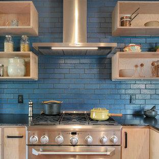 Idéer för att renovera ett mellanstort funkis svart svart kök, med släta luckor, skåp i ljust trä, granitbänkskiva, blått stänkskydd, stänkskydd i keramik, rostfria vitvaror, mellanmörkt trägolv, en halv köksö och brunt golv