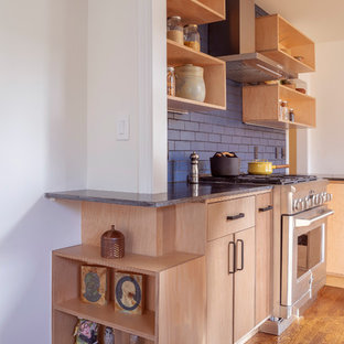Design ideas for a mid-sized modern l-shaped eat-in kitchen in San Francisco with an undermount sink, flat-panel cabinets, light wood cabinets, granite benchtops, blue splashback, ceramic splashback, stainless steel appliances, medium hardwood floors, a peninsula, brown floor and black benchtop.